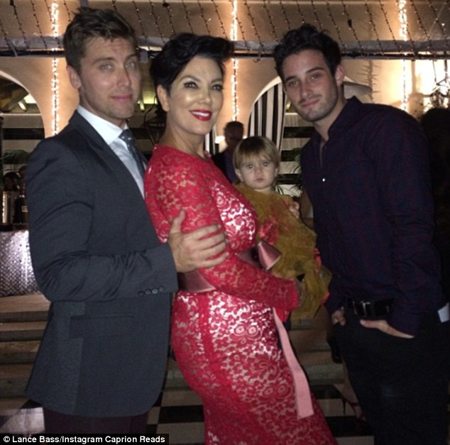 Dress disaster: Kris's white underwear was visible under the red lace as she posed with a friend's baby and singer Lance Bass and fiance Michael Turchin