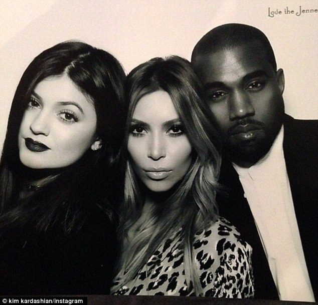 'Mi Familia:' Kim poses up next to her fiance Kanye and sister Kylie in the booth