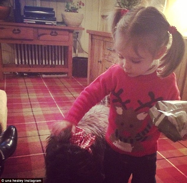 Adorable! Aiofe wears reindeer jumper whilst she plays with the dog at her dad's family home in Surrey