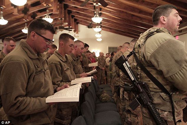 Praying for safe returns: American soldiers attend a religious ceremony at Bagram base in Kabul on Tuesday night