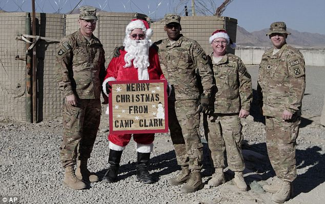 Spreading cheer: Major General James C. McConville (left) visited NATO troops in Eastern Afghanistan during his seventh-annual Christmas Eve visit to the region