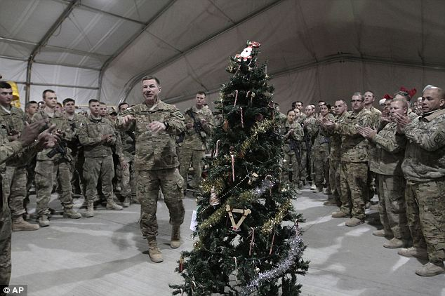 Keeping with tradition: Trees and decorations provide some of the similar trappings of Christmas for the thousands of soldiers who remain overseas, like these soldiers pictured in Logar province