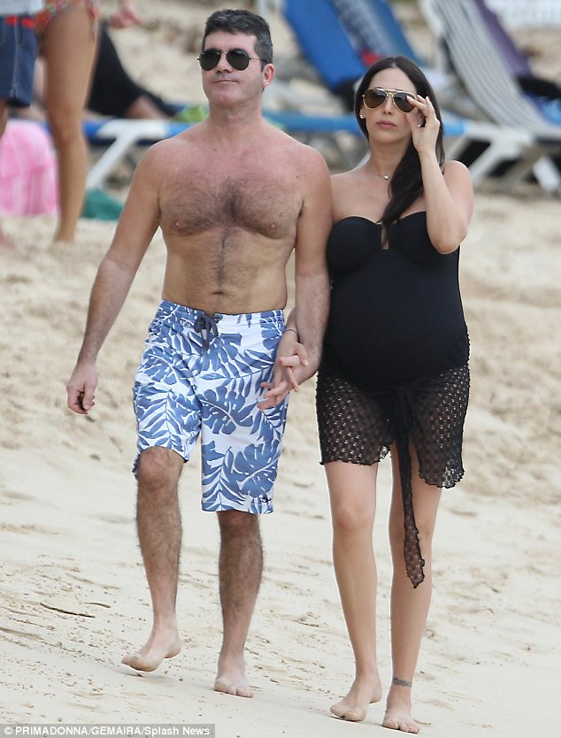 Pecs appeal: Simon's pectoral muscles were on display as he strolled on the beach shirtless