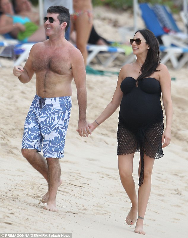 Domestic bliss: Simon Cowell and Lauren Silverman looked the picture of domestic bliss as they strolled hand-in-hand on the beach in Barbados during a Christmas vacation. They're now in St Barts