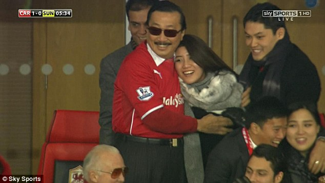 Happy man: Tan, dressed in Cardiff's controversial red home shirt, hugs one of his guests after watching his team take the lead