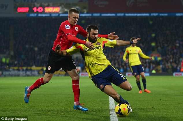 Battle: Cardiff's Craig Noone (left) challenges Sunderland defender Andrea Dossena (right) for the ball in the first half