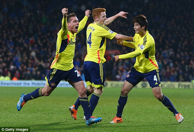 All smiles: Colback celebrates securing a point for Gus Poyet's struggling side with team-mates Emanuele Giaccherini (left) and Ki Sung-Yueng (right)