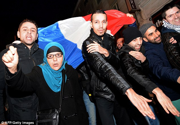 Defiant: A group performs the 'quenelle' salutes in front of the theatre Dieudonne's performing at