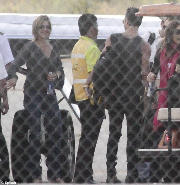 Ready to rumble: Aniston patiently awaits her entourage to board the shuttle so she can begin her vacation