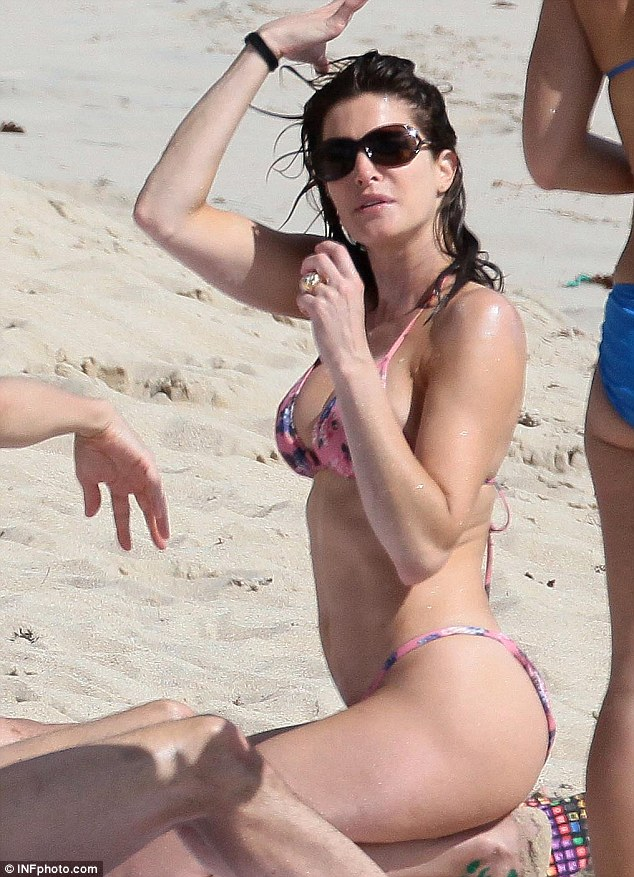 Beachside fashion: The star appeared to fix her hair after rubbing herself down with the sun protection