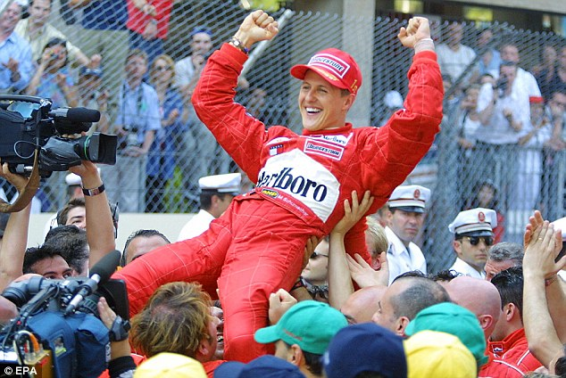 On top of the world: Schumacher is hoisted aloft by mechanics after winning the 2001 Monaco Grand Prix