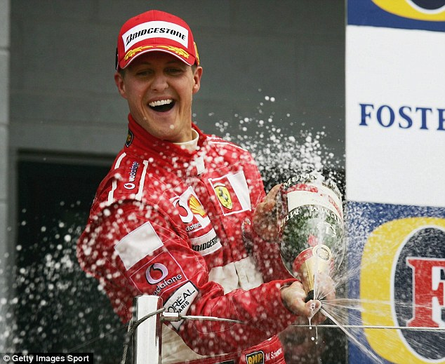 Champagne moment: Schumacher sprays the bubbly at Silverstone after pipping Kimi Raikkonen to victory