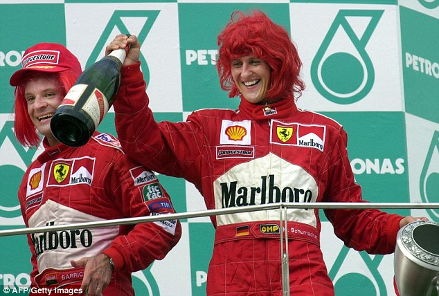 Sharing a joke: Schumacher and Rubens Barrichello celebrate another Ferrari one-two in Malaysia in 2000