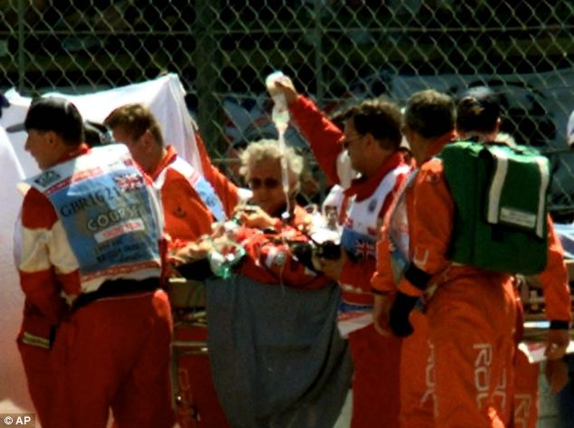Schumacher is carried on a stretcher by paramedics and track marshals, after he crashed his Ferrari during the first lap of the British Grand Prix at Silverstone in 1999
