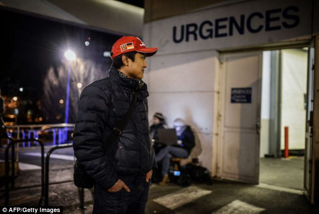 A Ferrari fan waits in front of the emergency department of the Centre Hospitalier Universitaire hospital, French Alps, where German seven times Formula one world champion Michael Schumacher is reported to be treated