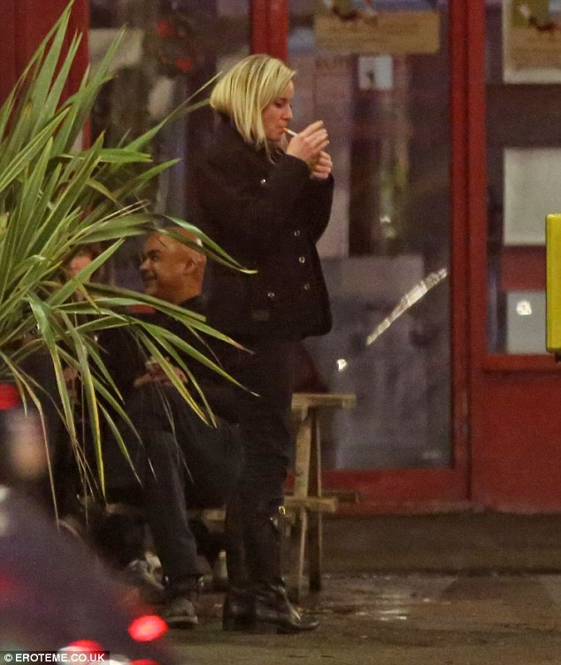 Lighting up: The actress was seen smoking outside the London pub with her friends sat near by