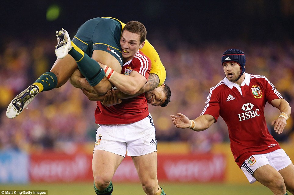 Power play: George North of the British & Irish Lions lifts his Aussie opponent Israel Folau and drives him backwards in an astonishing display of strength at Melbourne's Etihad Stadium as Leigh Halfpenny (right) supports on June 29