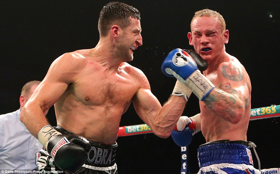 Controversial: Carl Froch (left) punches George Groves during their world title fight in Manchester in November. Froch won the fight when referee Howard Foster stopped it prematurely in the ninth round when Groves came under pressure