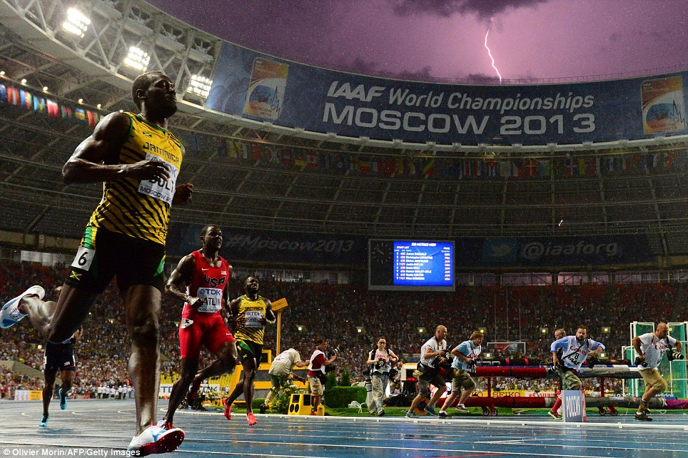 Lightning bolts: Usain Bolt (left) wins the 100 metres final in 9.77sec at the World Championships in Moscow on August 11 as lightning flashes  across the sky. Justin Gatlin claimed and Nesta Carter, like Bolt from Jamaica, took bronze