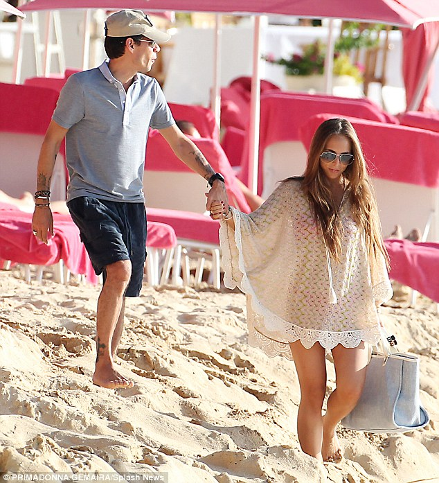 Effortlessly chic: Showcasing her toned and tanned pins as she wandered down the beach with her man, Chloe kept her bikini body under wraps in a stylish semi-sheer beige kaftan, featuring pretty embroidered detailing