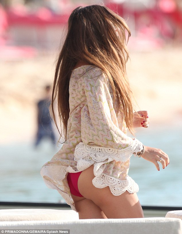 Cheeky! And as a sudden gust of Caribbean breeze whipped up the side of her kaftan, Chloe's skimpy scarlet bikini bottoms and toned derriere could be seen underneath