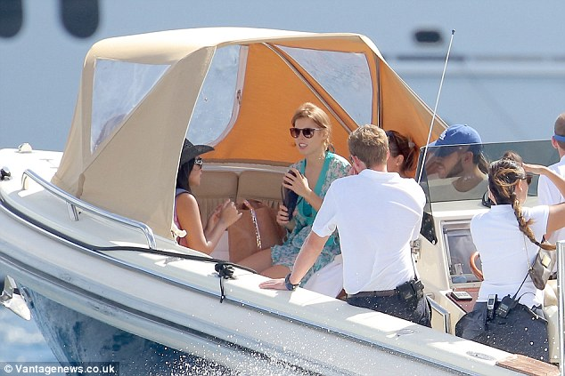 At sea: The 25-year-old clung onto her flip-flops as she made her way to the yacht on a smaller boat