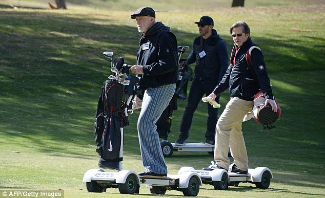 All revved up: Ex-European Tour player Chris van der Velde (right) and 80-year-old Don Wildman ride GolfBoards, which are designed to make golf cool and are controlled by handheld devices as well as riders leaning to steer the boards