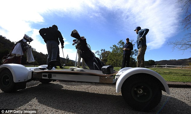 Test drive: A GolfBoard is parked beside a green at the Malibu Golf Club last month. Gearboxes housed on each end of the board provide power to all four wheels evenly so that it won't slip on the steepest hills and stops 'spinouts' on the golf course, which can mark the green