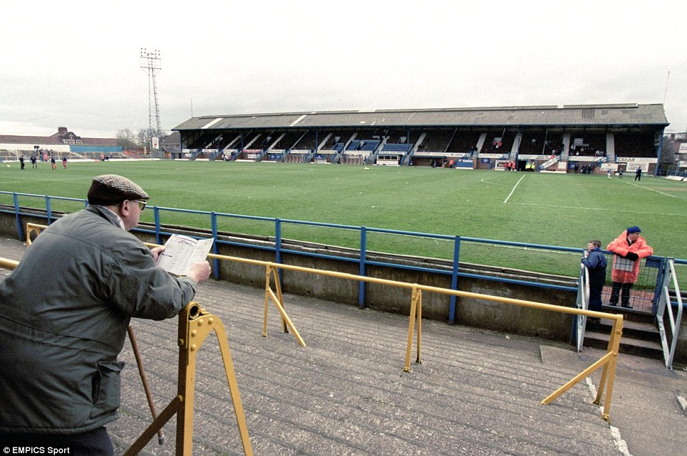 A Chesterfield fan reads his programme as he waits for the players to emerge onto the pitch