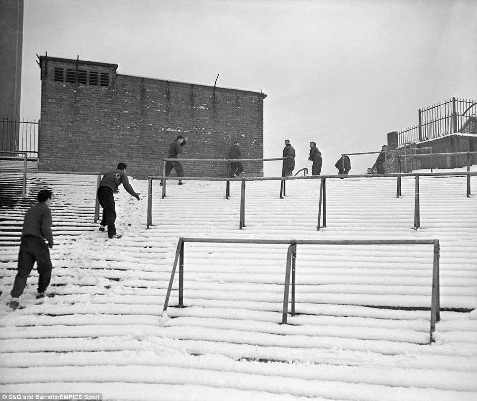 Arsenal players find plenty of ammunition for a quick snowball fight as they make their way over the snow-covered terraces to their training pitch, having discovered that their match had been postponed due to the wintry weather