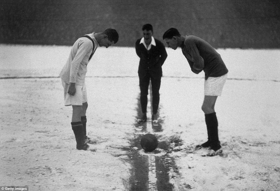 16th January 1926: The referee tosses up on a snow-covered football pitch at the start of the football match between Arsenal and Manchester United at Highbury.   (Photo by H F Davis/Getty Images)