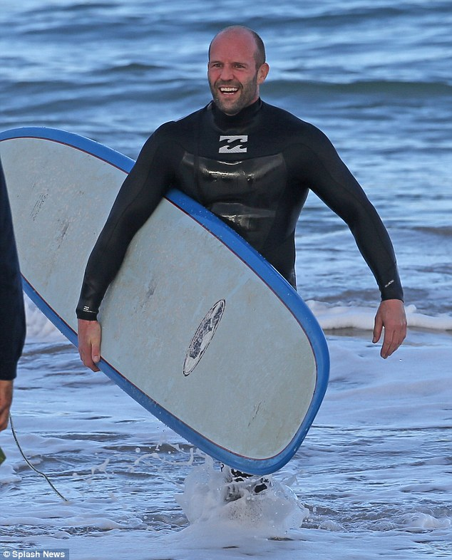 Happy New Year: Jason Statham went surfing in Hawaii on Wednesday