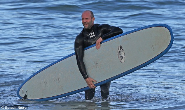 Fresh: Meanwhile Jason was spotted hitting the waves for some surfing