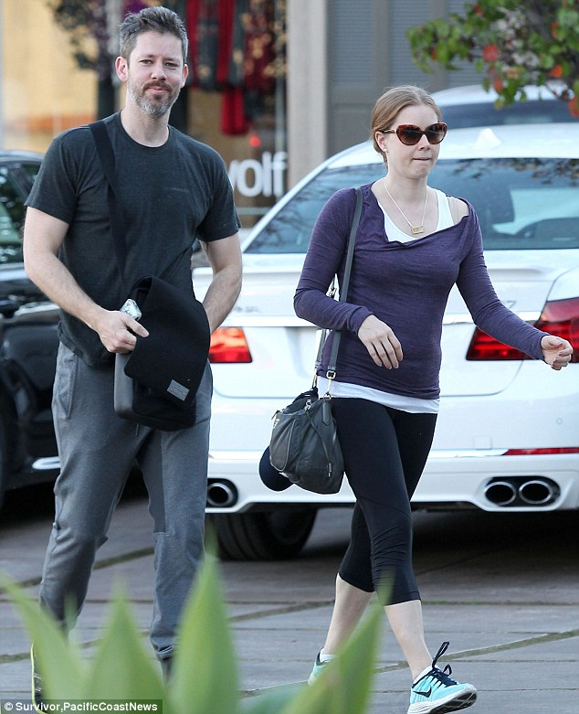 Workout chic: Amy looked stylish in her off-duty outfit of leggings, a white vest top and purple long-sleeved top for the outing
