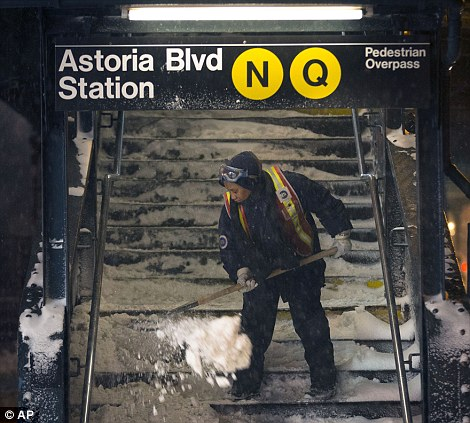 A worker clears snow from a stairway at the Astoria Blvd subway station in the Queens borough of New York early on Friday morning