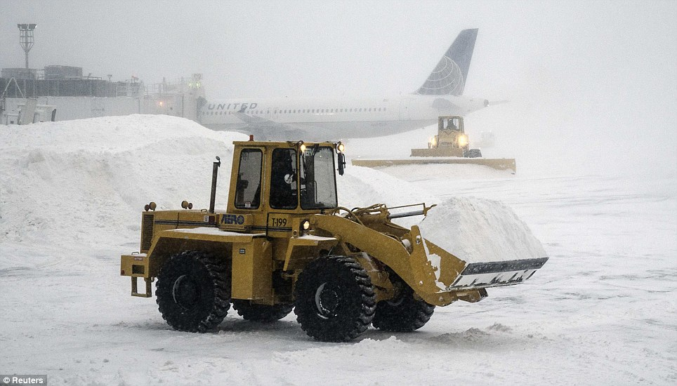 Heavy machinery clears the snow at LaGuardia Airport in New York City. Thousands of flights were canceled over Thursday and Friday