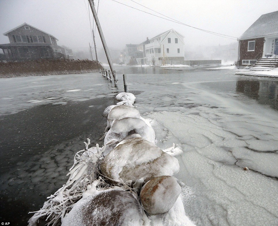 Houses line a flooded street along the shore in Scituate, Massachusetts on Friday as a winter storm dropped nearly 2 feet of snow just north of Boston, shut down major highways in New York and Pennsylvania and forced U.S. airlines to cancel thousands of flights nationwide