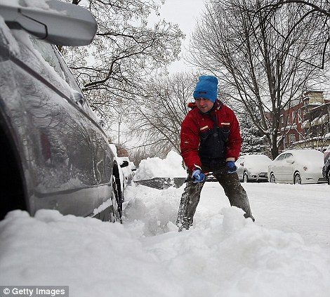 A man digs his car out in Brooklyn following a snow storm