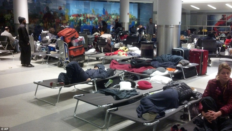 Passengers stranded at New York's JFK Airport rest on cots in American Airlines' Terminal 8 on Friday after the cancellation of hundreds of flights
