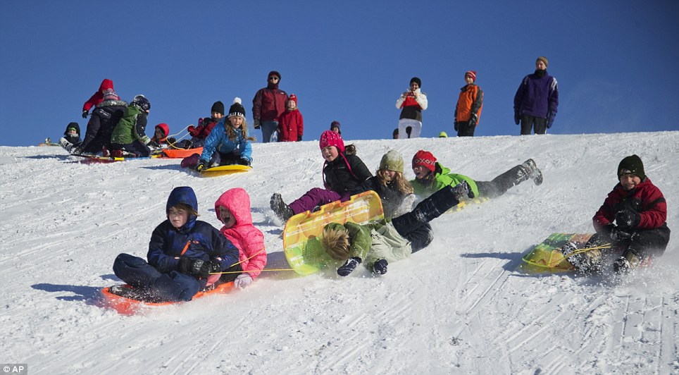 Children race downhill a slope on sleds in Silver Spring, Maryland on Friday as they were given a day off school