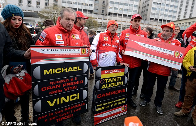 Tribute: Fans of Schumacher hold signs with messages of support and banners of F1 Ferrari team