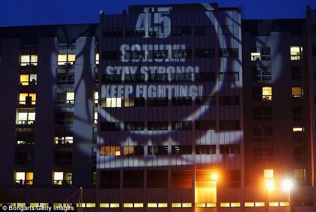 Statement: Fans project a message on a wall of the Grenoble Hospital which reads: '45. Schumi stay strong! Keep fighting'