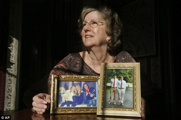 Penny Trusty, 74, a retired software designer poses with photographs of her five grandchildren in her home in Rockville, Maryland