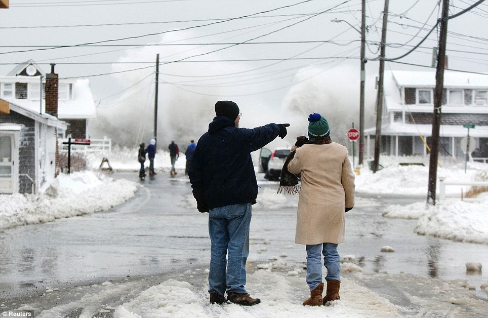 Two people watch the waves crash in the distance during a winter snow storm in Scituate, Massachusetts, where coastal flooding was now a serious threat