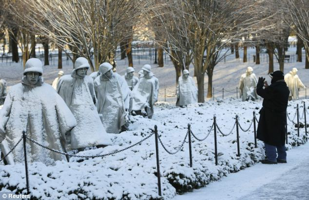Blanketed: A man takes a photo at the Korean War Memorial in D.C., which saw several inches of snow