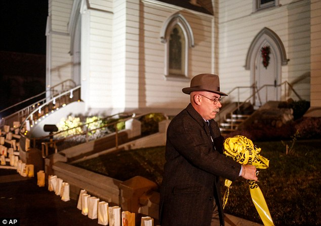 Sergeant Bill Nova removes tape from the police murder scene turned memorial for a brutally slain priest last week