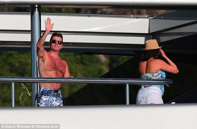 We're off: Cowell and Lauren make their way inside after admiring the view from the boat's top deck