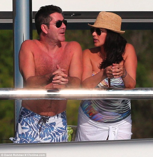 Plenty to talk about: Cowell enjoys and idle chat with pregnant Lauren while they lean against the $73 million yacht's railings
