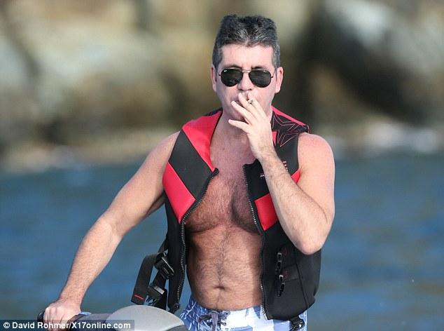 Multitasking: The mogul takes a greedy puff while navigating his jet-ski