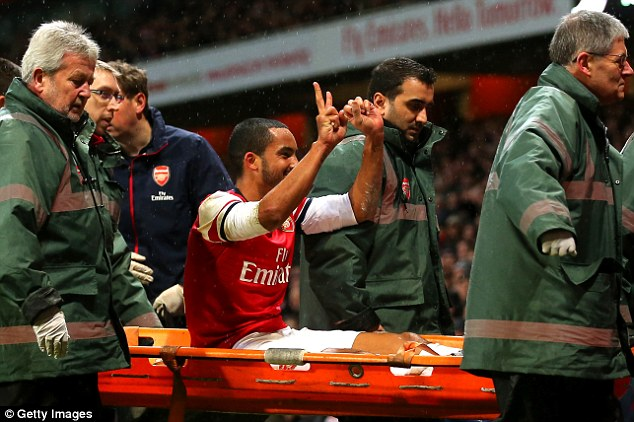 Reminder: Injured Theo Walcott taunts Tottenham fans with a 2-0 gesture as he is stretchered off